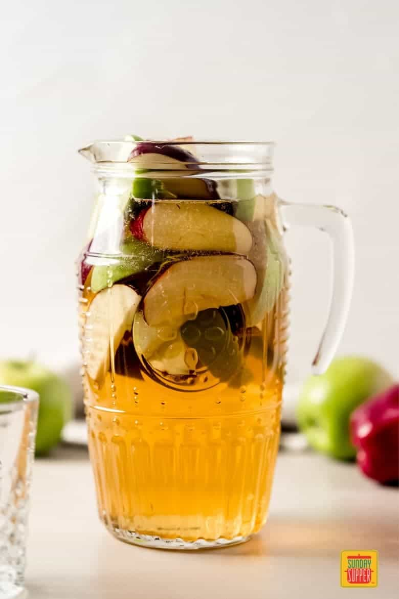 a pitcher of caramel apple sangria filled with apple slices