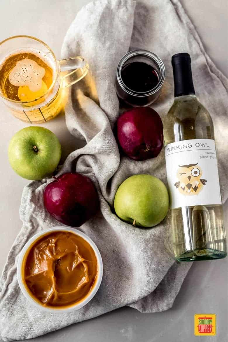 the ingredients to make caramel apple sangria on a table with a linen towel