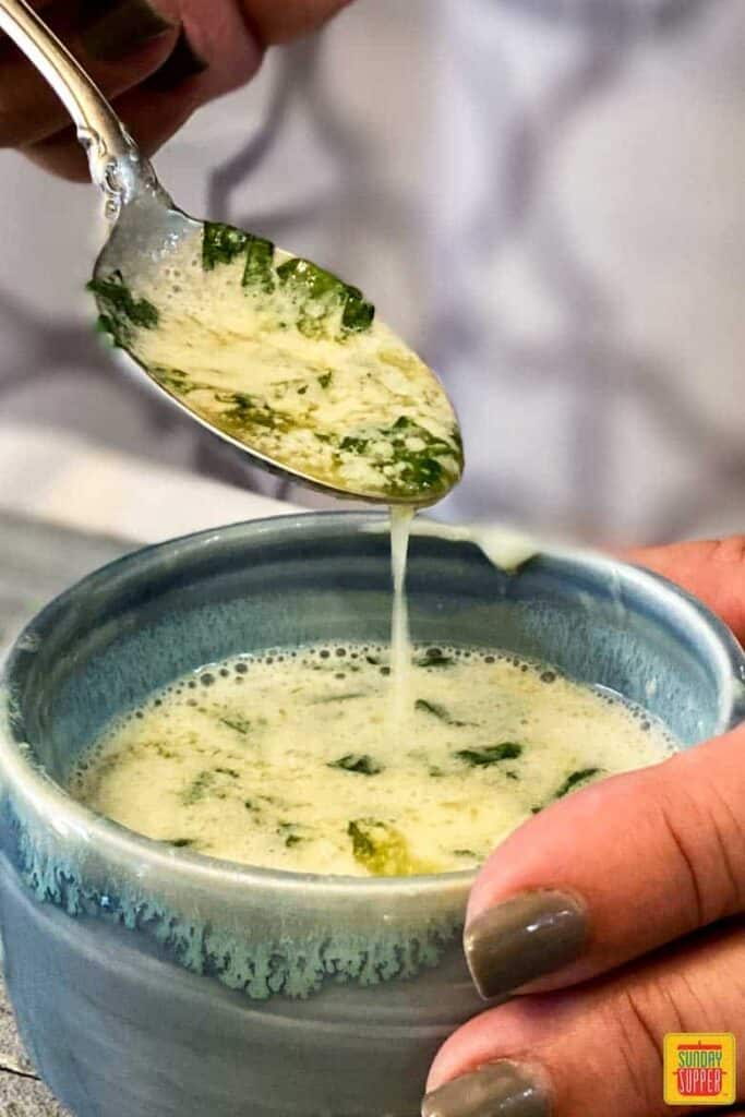 Garlic butter sauce dripping from a spoon