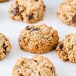 Six oatmeal raisin cookies on a white surface