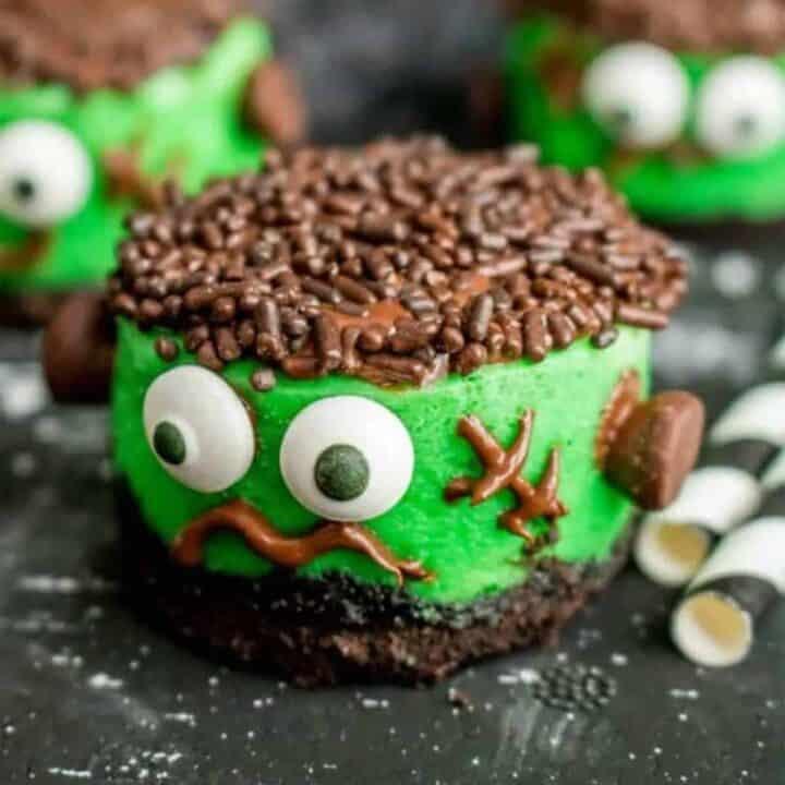 Mini Frankenstein cheesecakes on a black surface