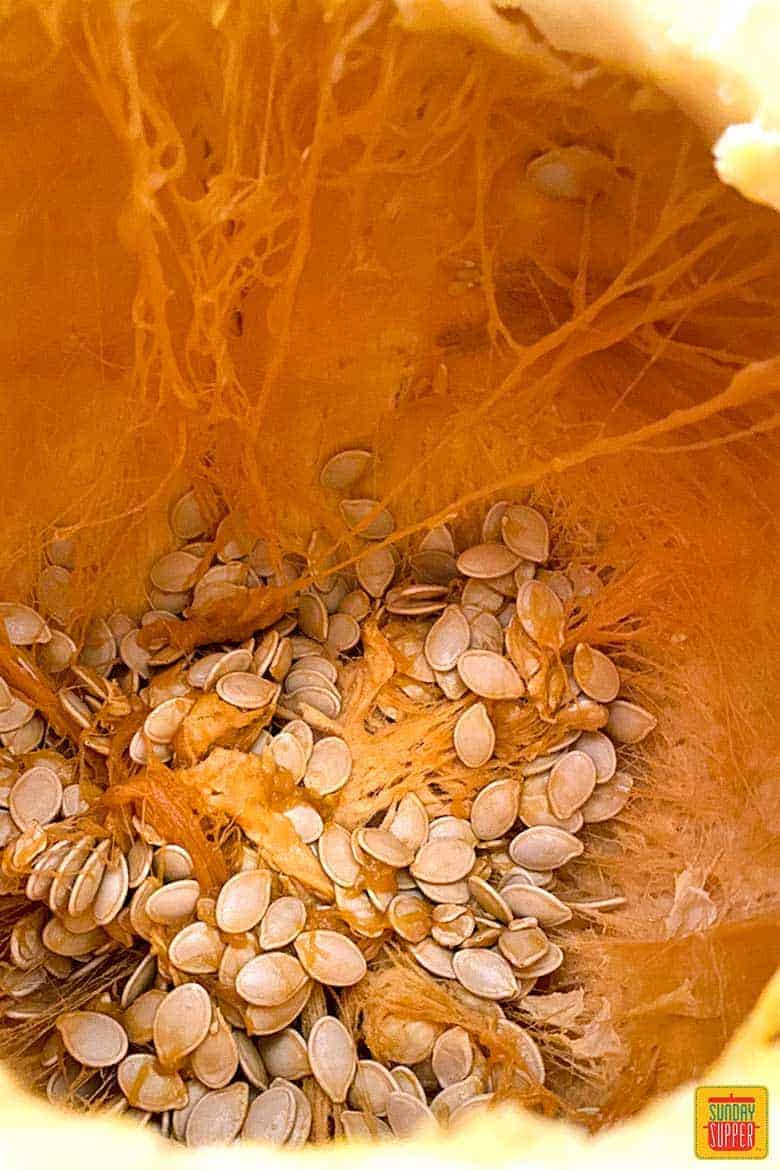 Pumpkin seeds inside of a pumpkin