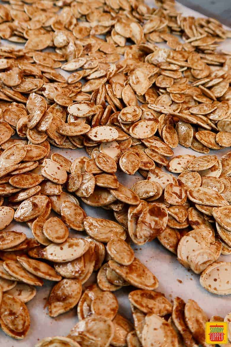 Roasted pumpkin seeds on baking sheet after roasting
