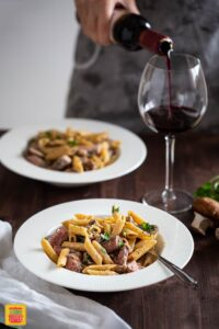 Creamy Penne Pasta with Sliced Prime Rib served in a plate with wine being poured on the side