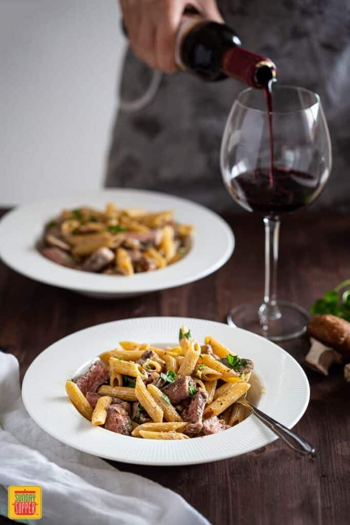 Creamy Penne Pasta with Sliced Prime Rib served in a plate with wine being poured on a side