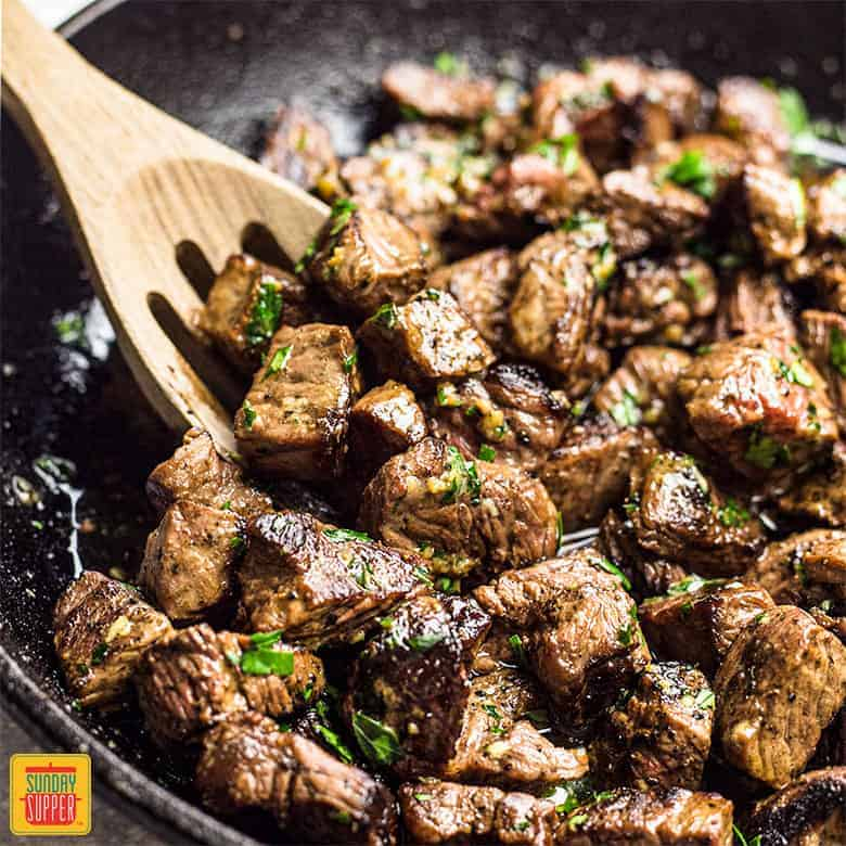 garlic butter steak bites in a black skillet with a wooden slotted spoon
