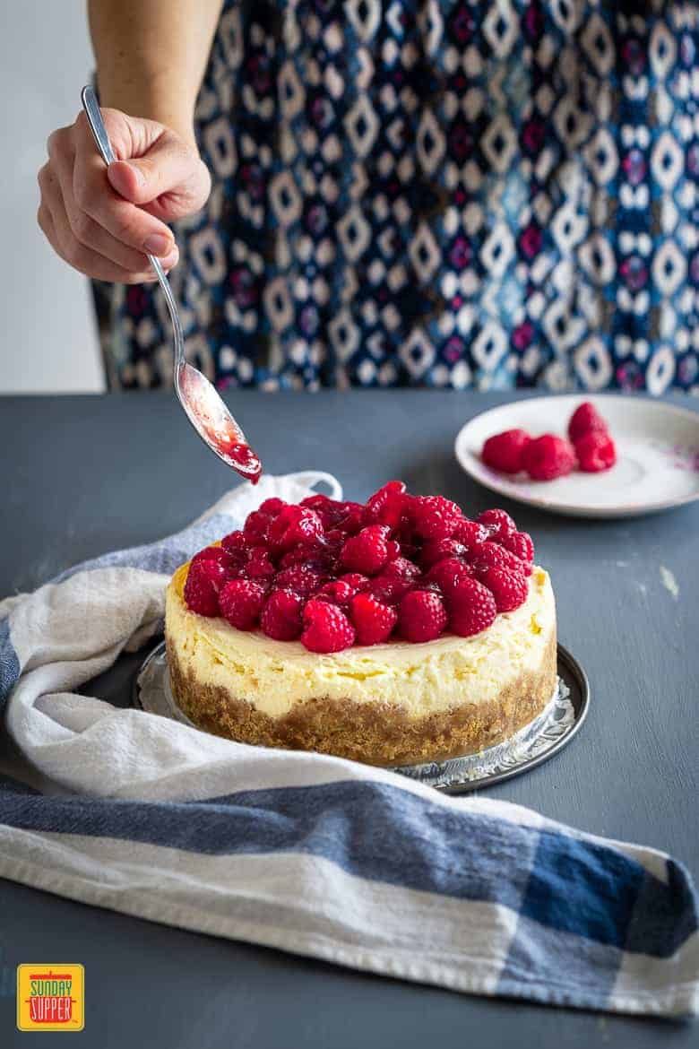 Instant Pot Cheesecake being decorated with raspberries and jam