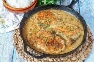 Southern smothered pork chops in a cast iron skillet