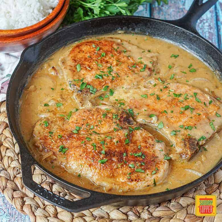 Smothered Pork Chops in a cast iron pan