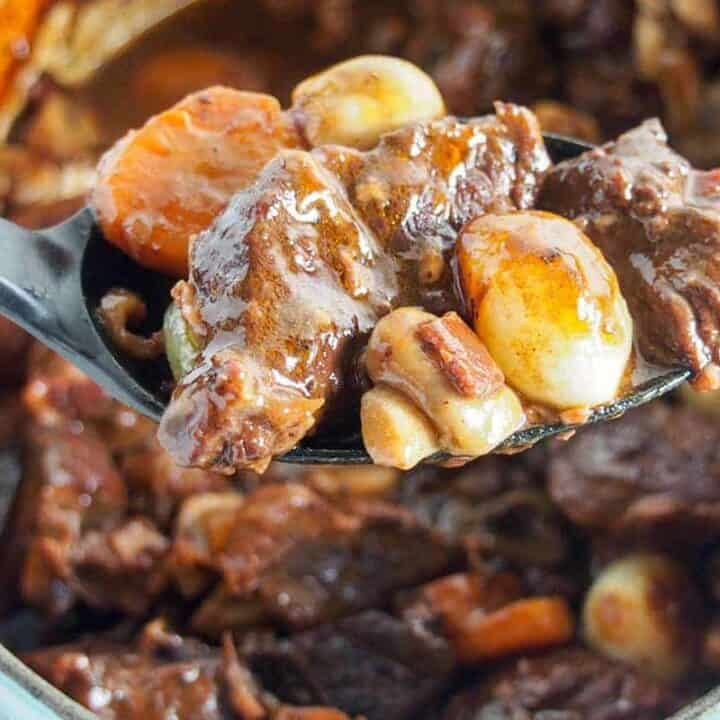 easy beef bourguignon recipe with spoonful held over pot