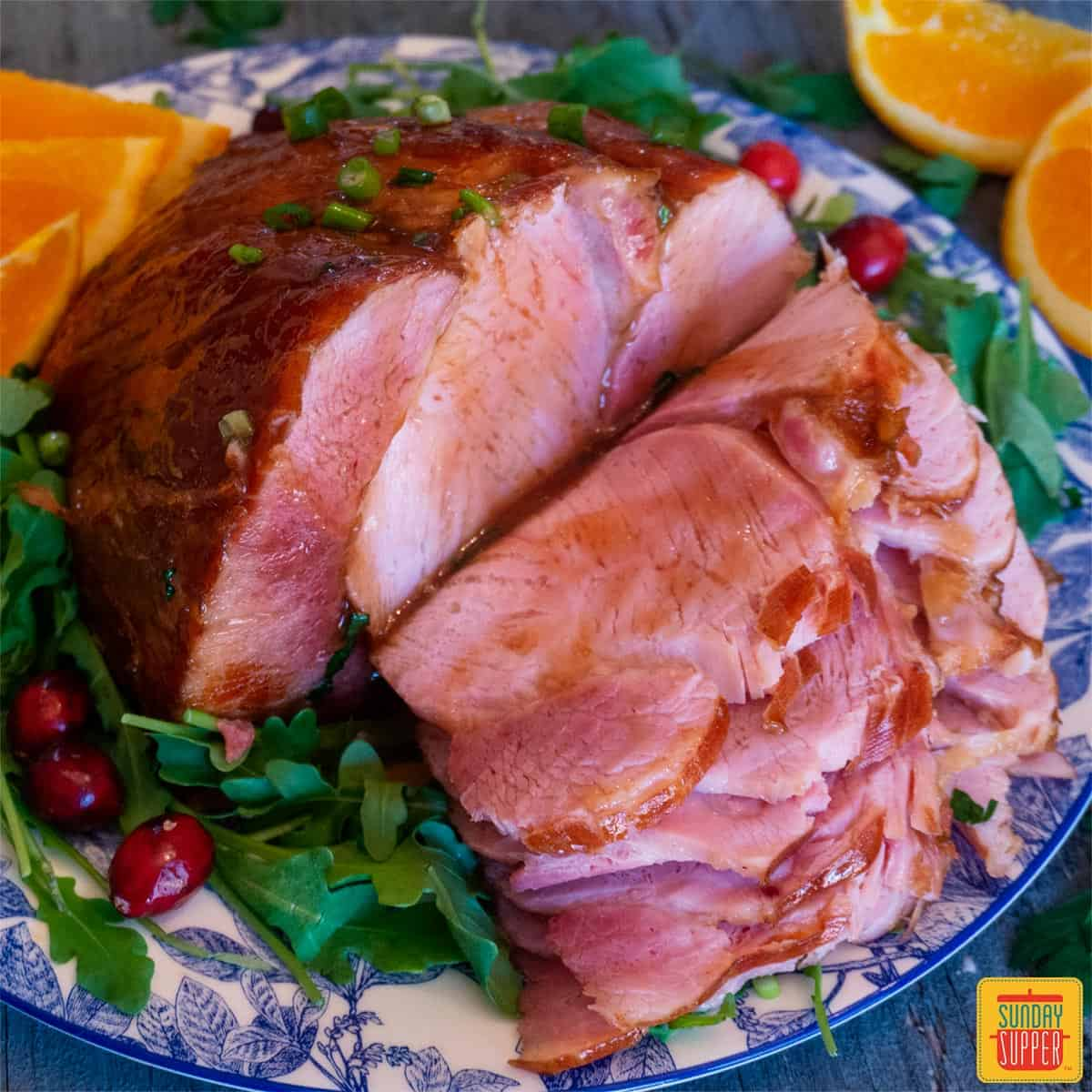 Close up of honey glazed ham slices with greens and oranges