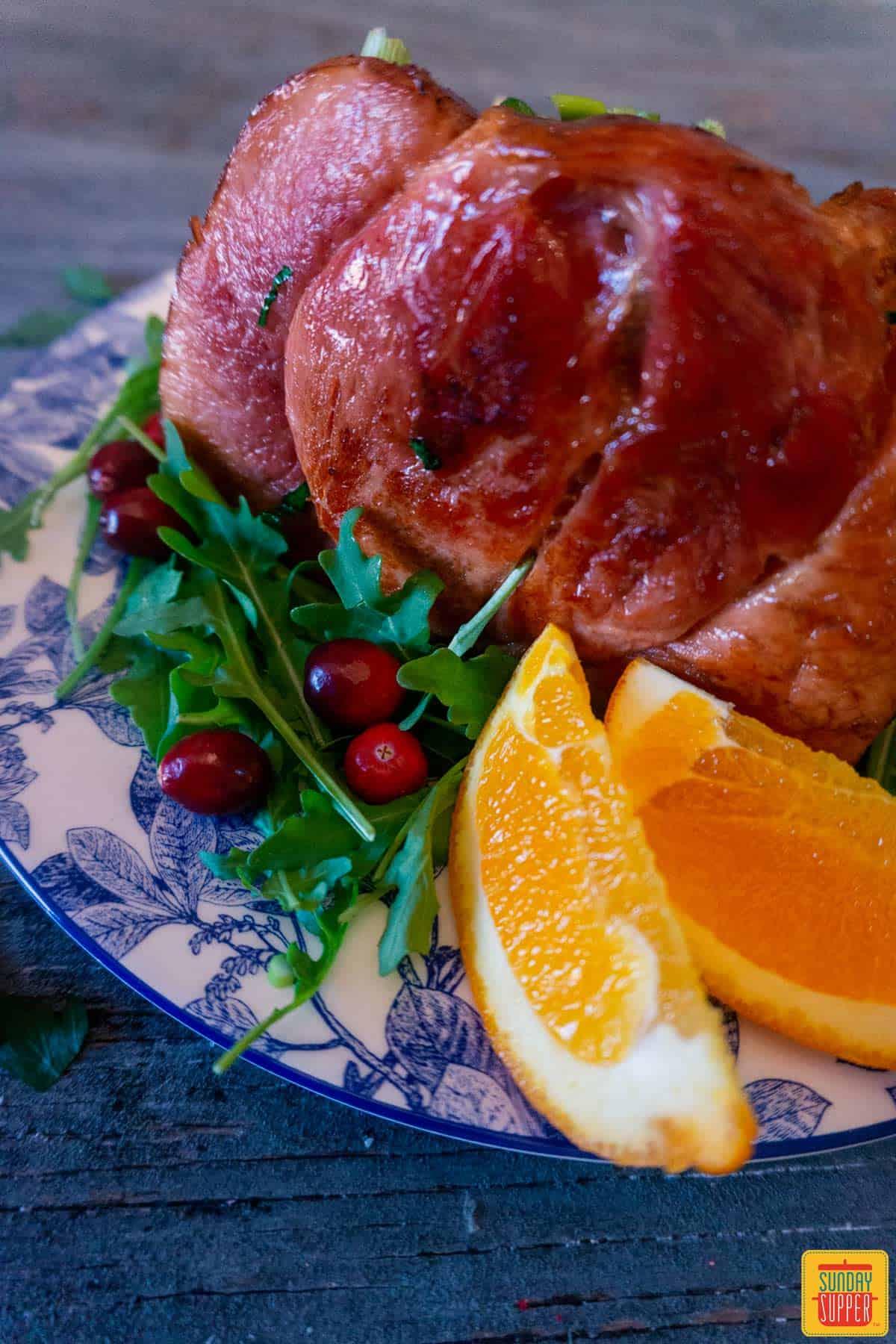 Close up of honey glazed ham with orange wedges