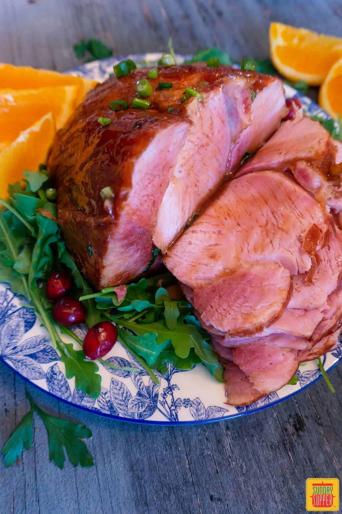 Sliced honey glazed ham with extra glaze on a platter