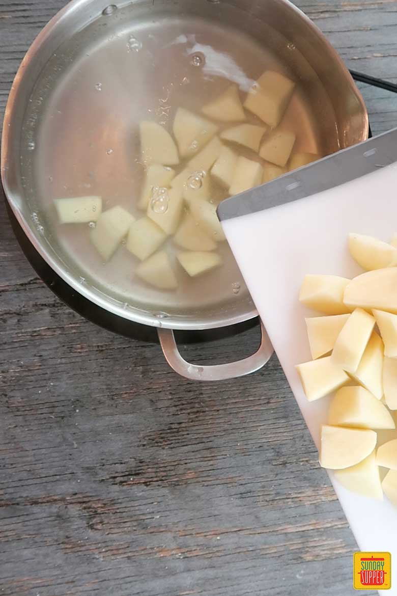 Adding potatoes to a pot of boiling water