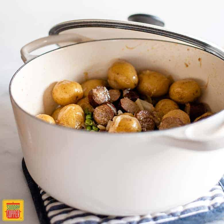 White dutch oven with smoked sausage and smothered potatoes