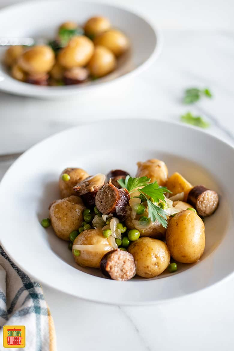 Onions, sausage, potatoes, and peas in a white bowl ready to enjoy