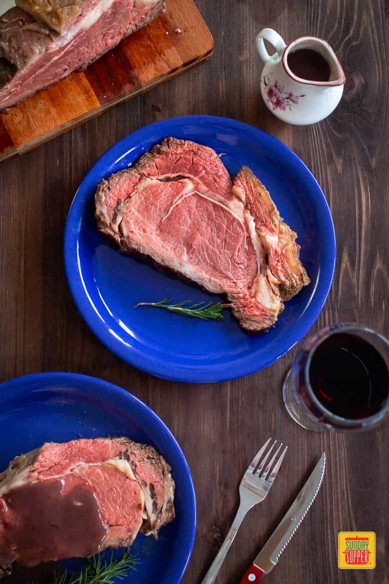 two blue plates of prime rib roast