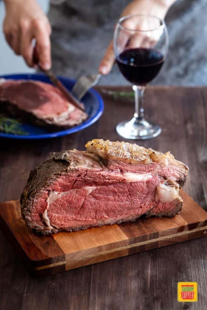 reverse sear prime rib on a cutting board with a glass of red wine