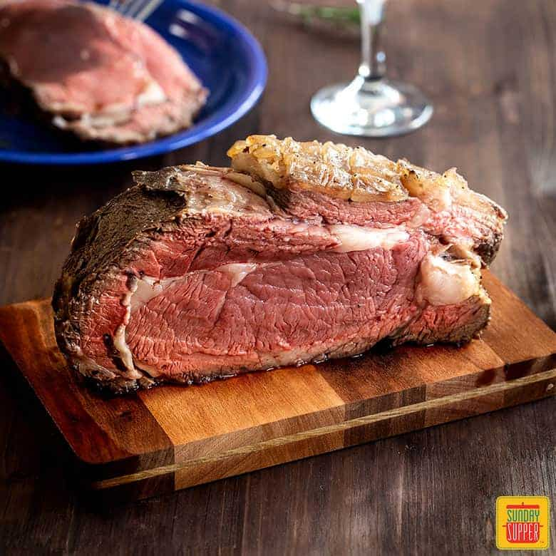 Beautifully cooked prime rib recipe on a cutting board with a slice of prime rib in the background on a blue plate and a glass of wine