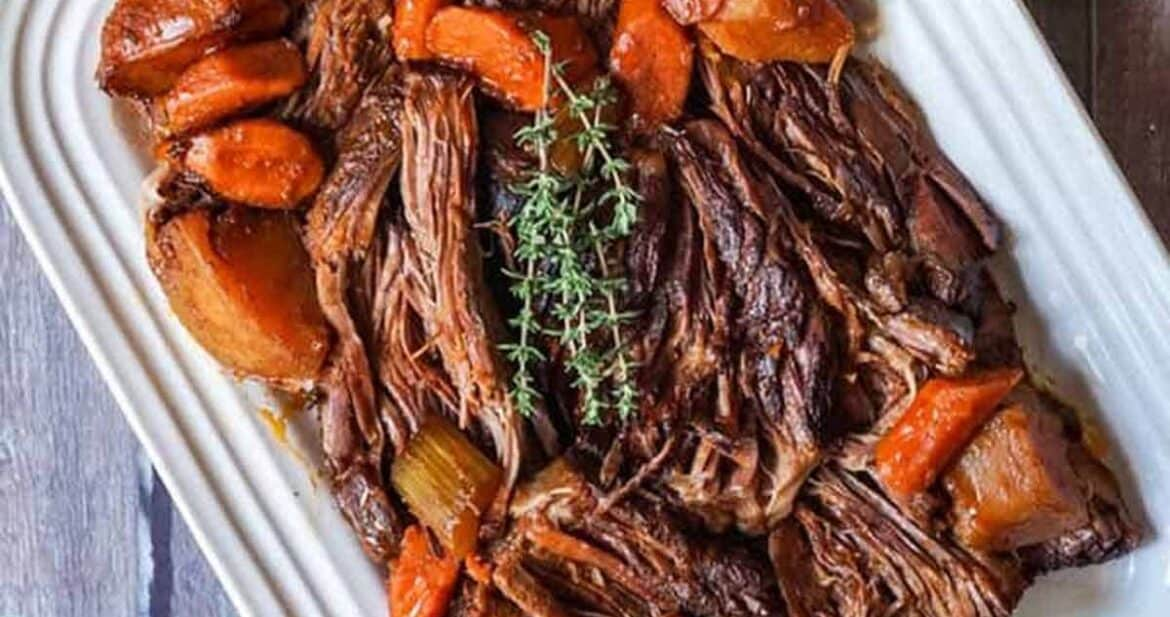 Overhead shot of beef chuck roast recipe on a white platter with carrots and fresh herbs