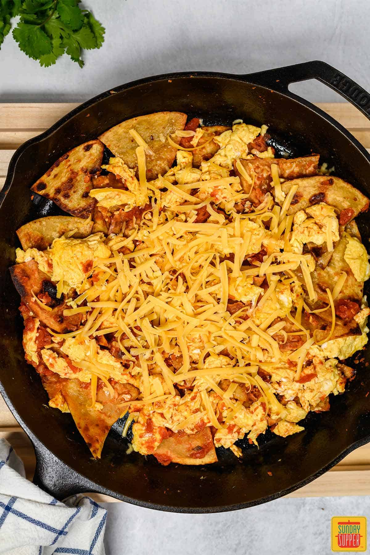 Tortillas and eggs mixed with cheese and salsa in a cast iron pan