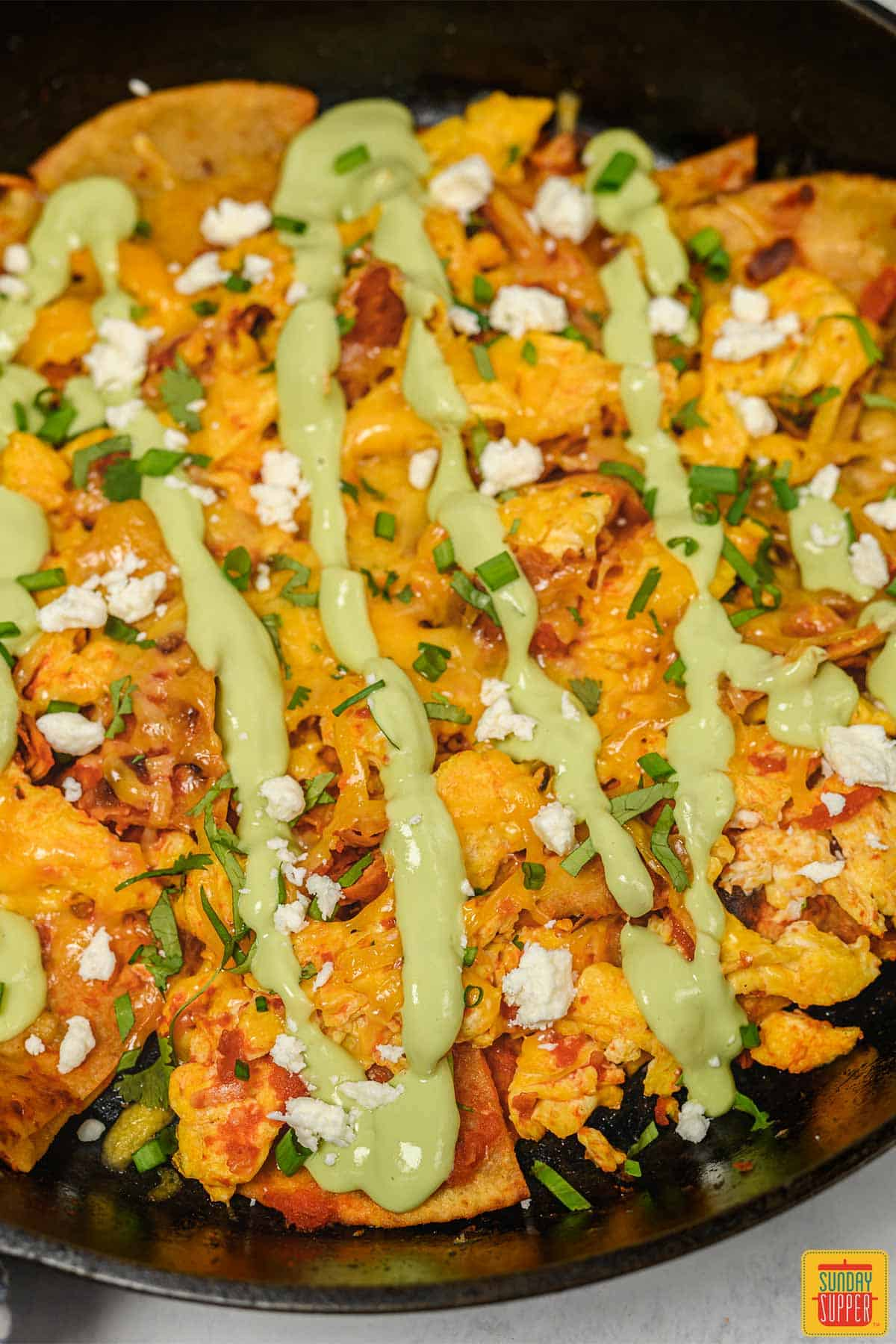 Close up of chilaquiles rojos in a cast iron skillet with avocado crema drizzled on top