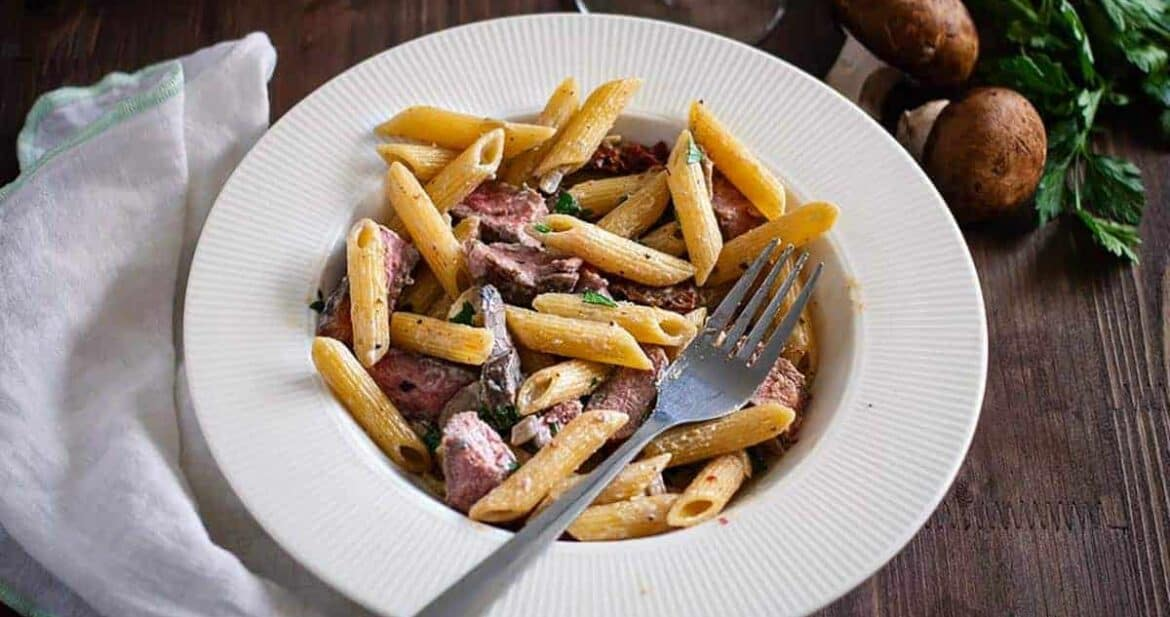Creamy penne pasta with sliced prime rib on a white plate with a fork