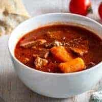 Instant pot Beef stew in a white bowl with a piece of bread and tomatoes