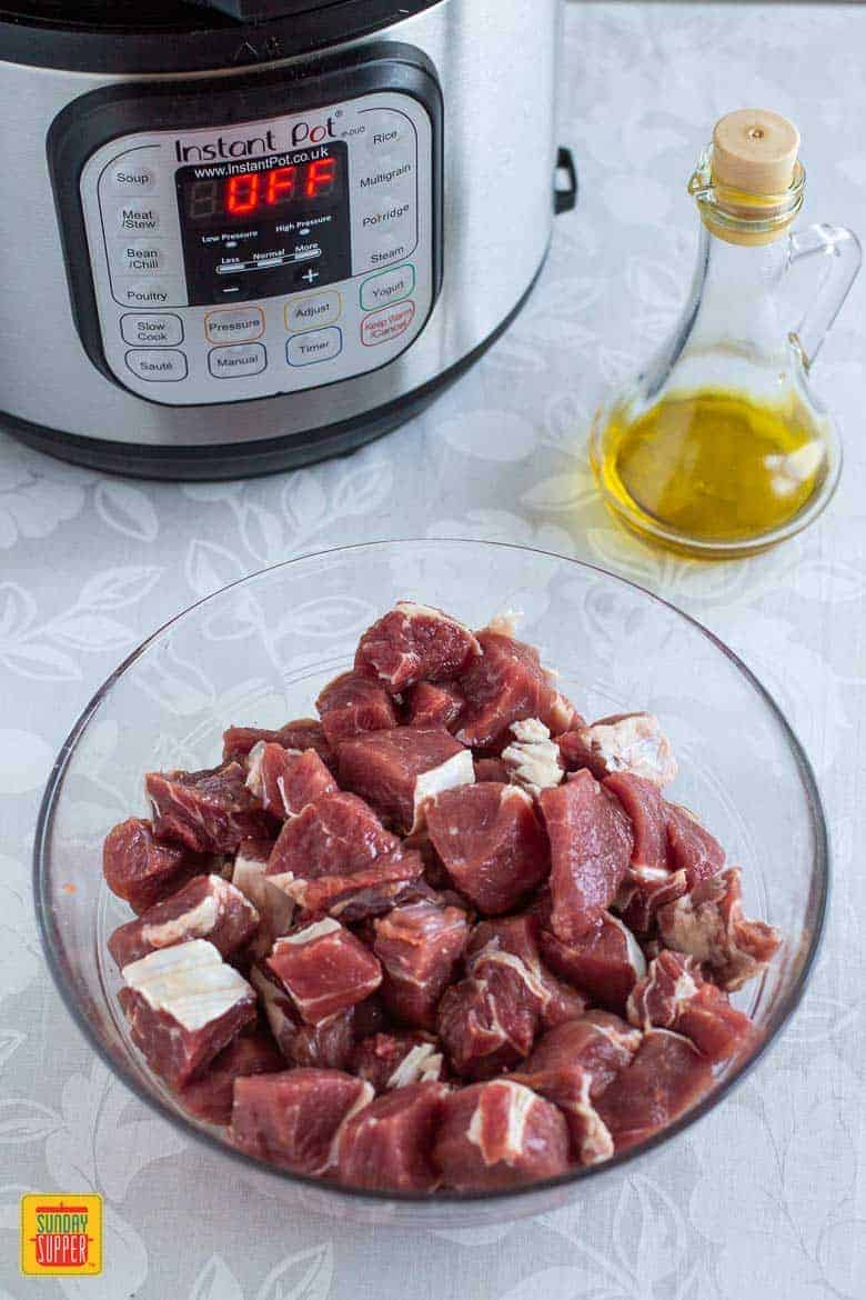Meat for instant pot beef stew in a glass bowl