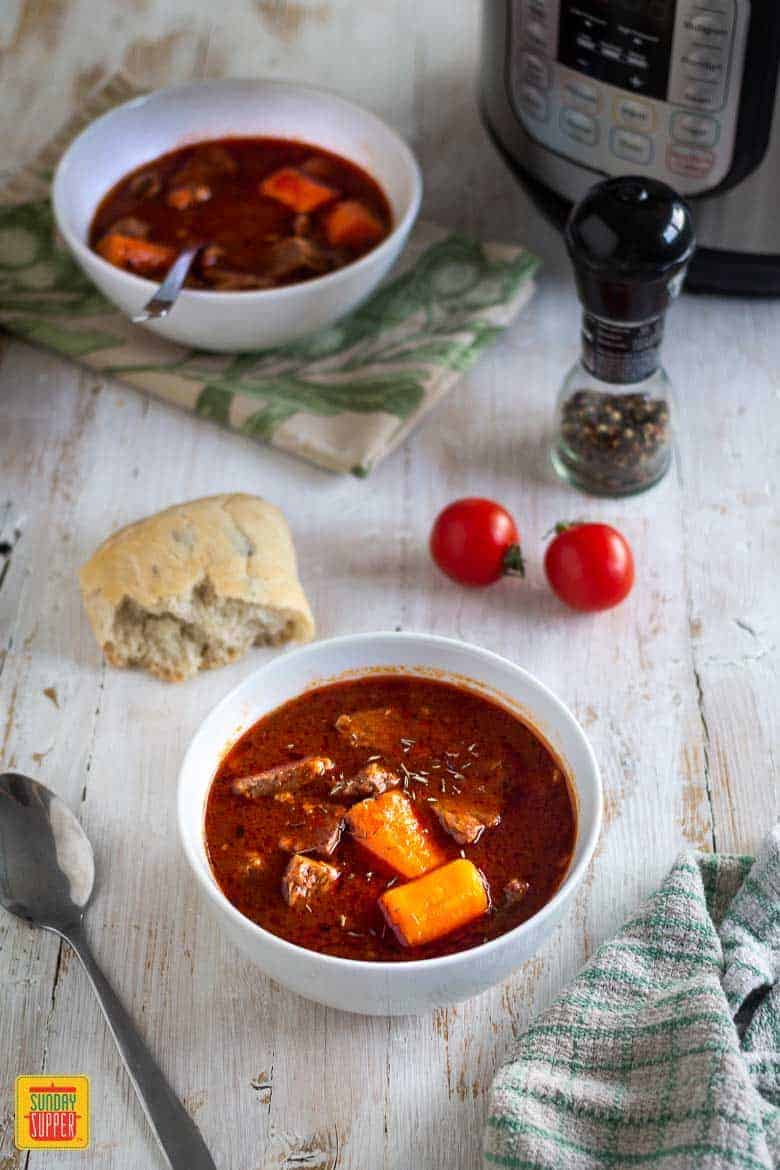 Two white bowls of Instant Pot beef stew with a piece of bread and two tomatoes