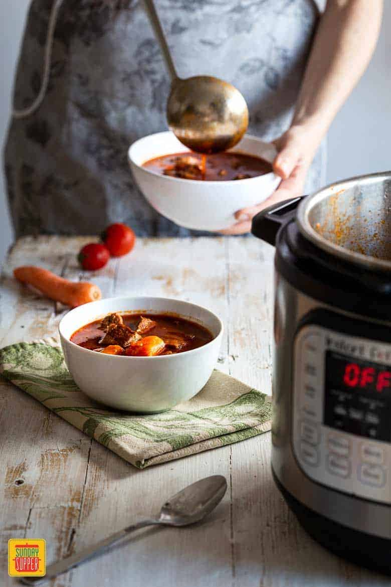 Ladling pressure cooker beef stew into a white bowl