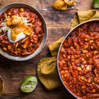 Bowl of the best chicken chili next to the pot of chili