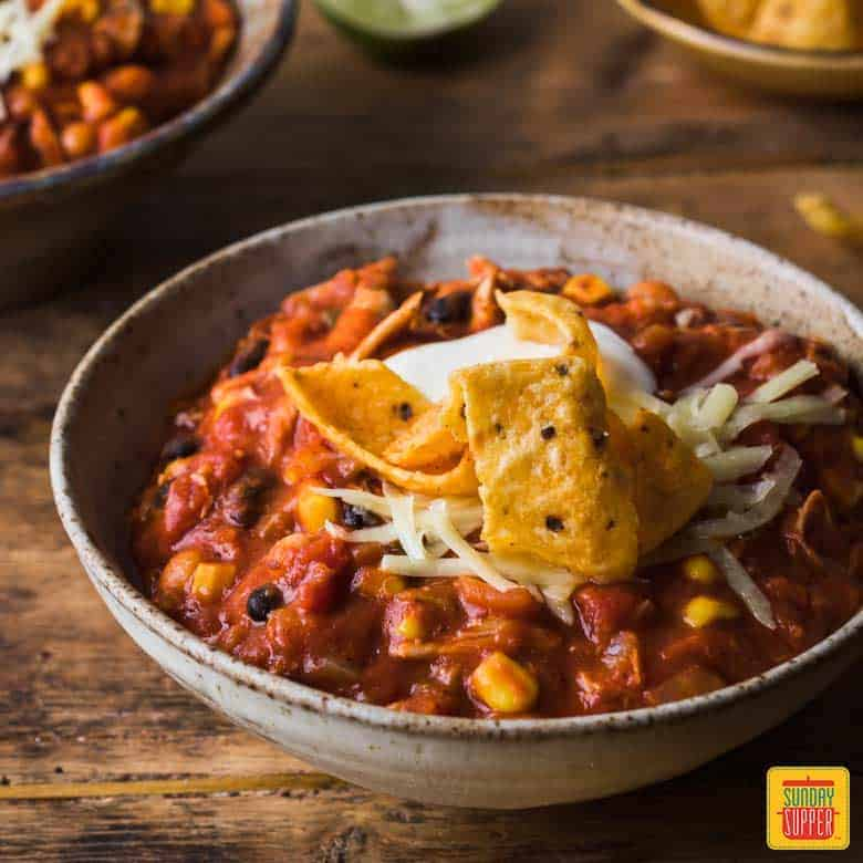 Best Chicken Chili Recipe: Bowl of chicken chili topped with sour cream and tortilla strips