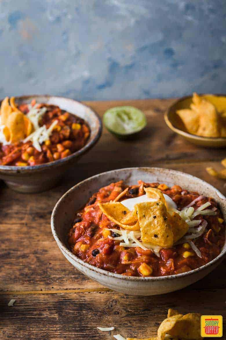 Two bowls of chicken chili with sour cream and tortilla strips
