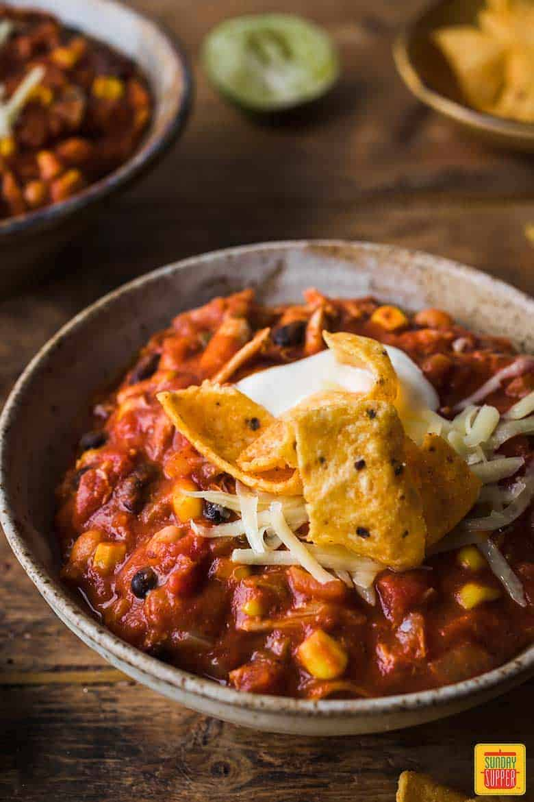 Close up of the best chicken chili recipe in a bowl with frito chips and sour cream