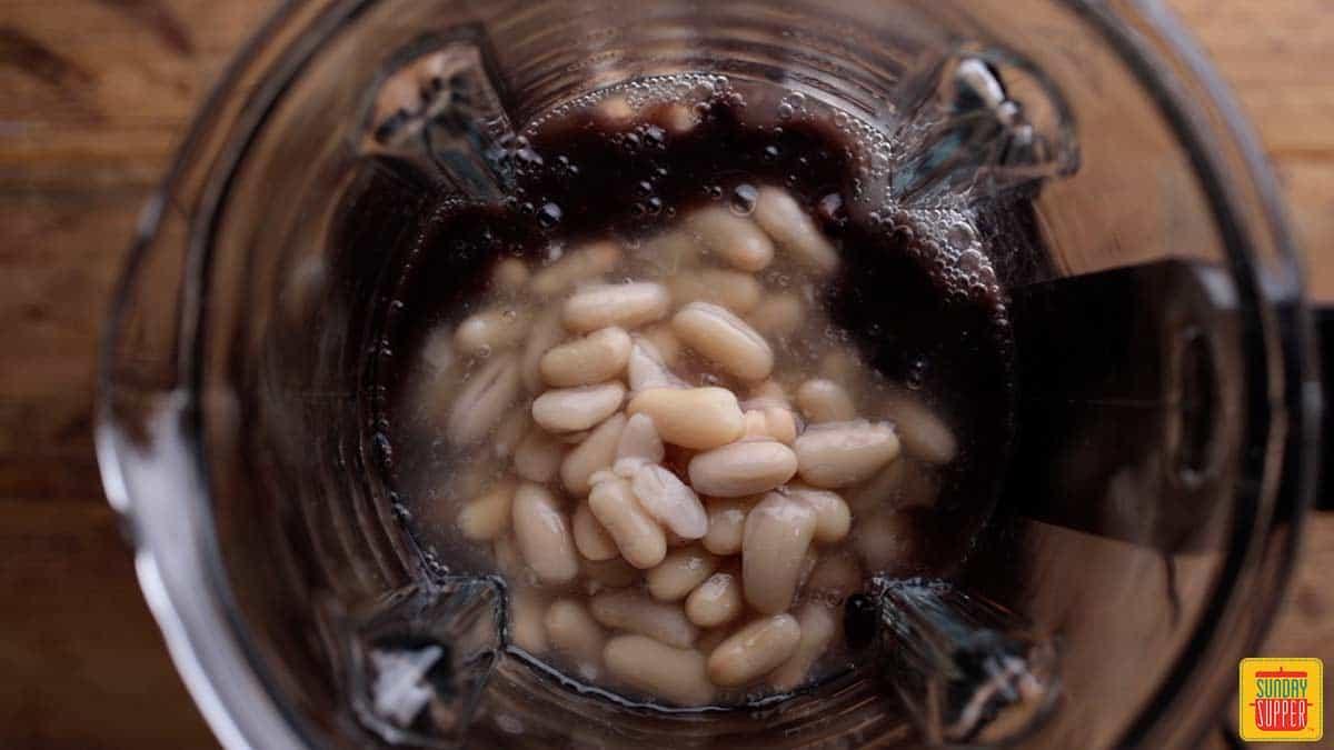 Adding beans to blender for best chicken chili recipe