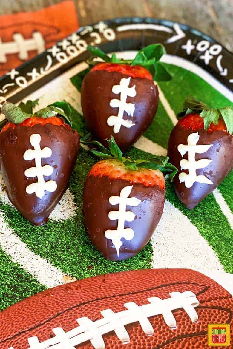 Four football chocolate covered strawberries