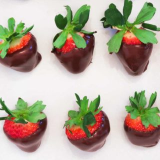 How to Make Chocolate Covered Strawberries: Six chocolate dipped strawberries in a row of three each on parchment paper