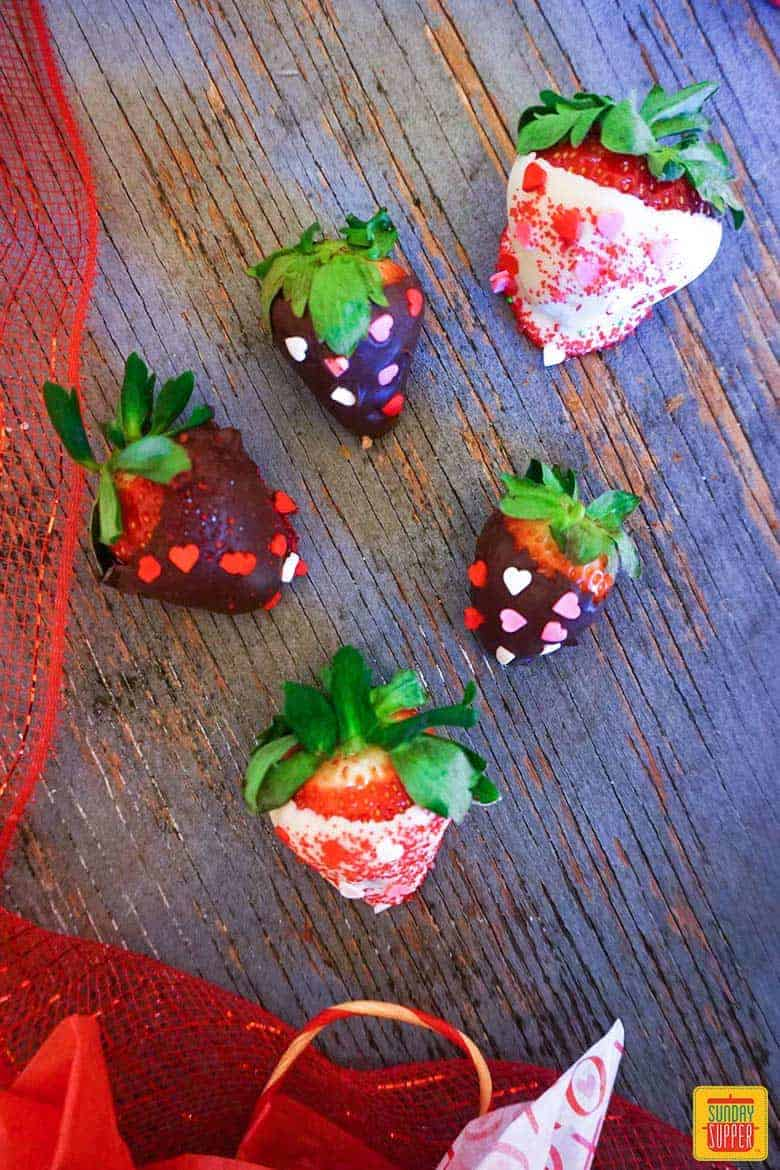 Five chocolate covered strawberries with heart sprinkles