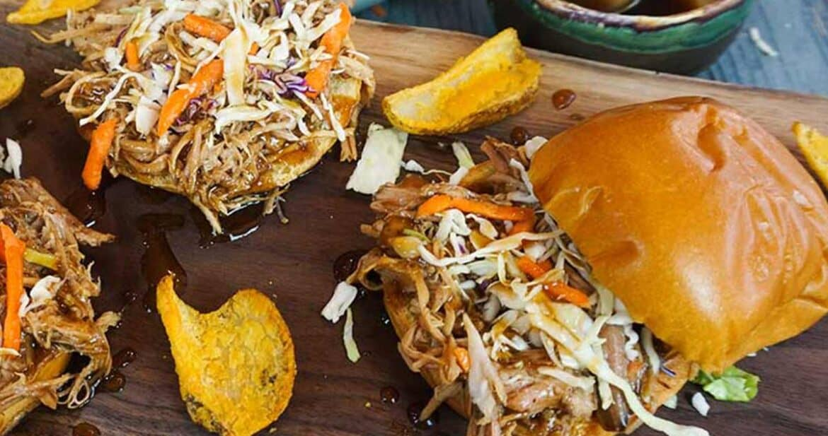 How to Make Pulled Pork: Three pulled pork sliders on a cutting board with potato wedges