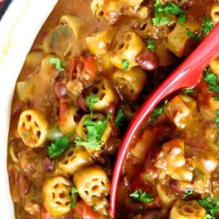 Chili mac recipe in a pot with a red ladle