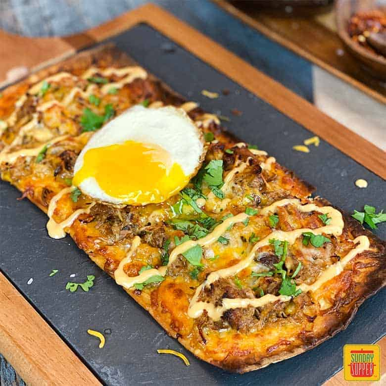 Pulled Pork Pizza Flatbread Recipe on a black serving board