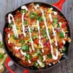 Sour cream drizzled over baked nachos