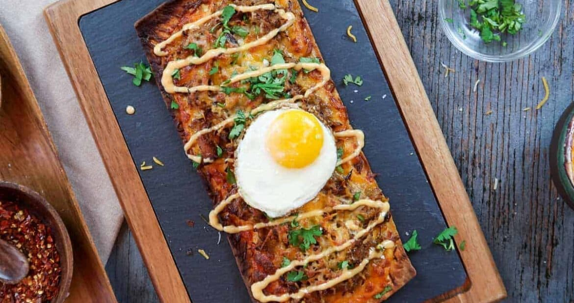Pulled pork pizza flatbread recipe on serving board with fried egg on top
