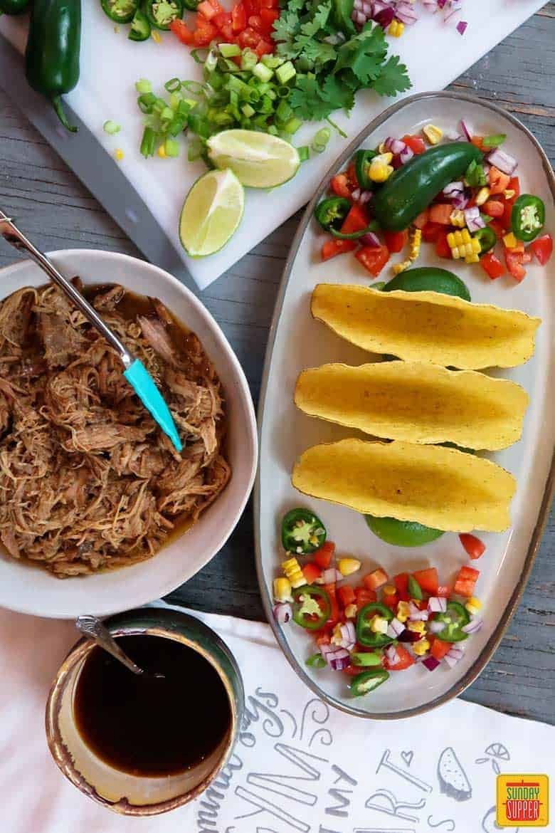 Taco shells and ingredients for pulled pork tacos
