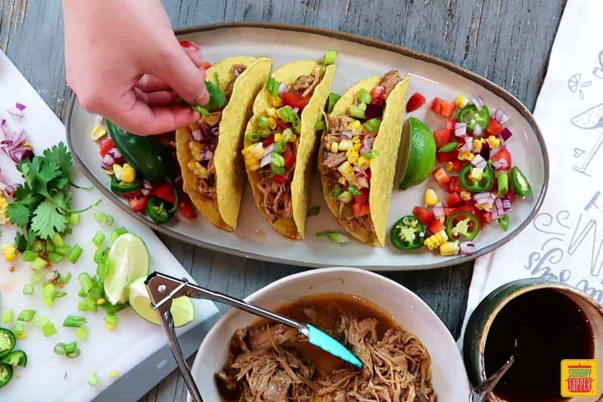 Adding toppings to pork tacos