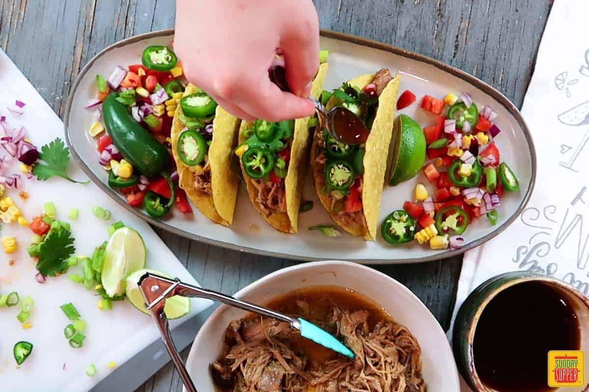Adding Jalapeno and cilantro to tacos.