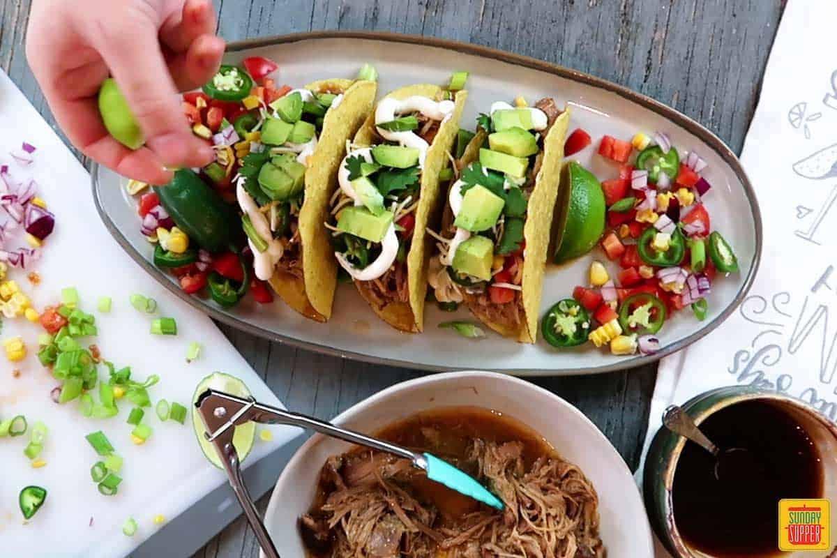 Adding avocado to pulled pork tacos