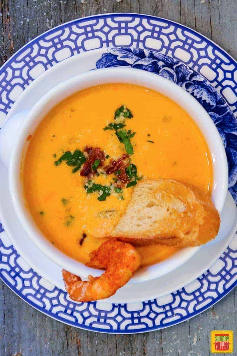 Shrimp bisque in a white bowl with crusty bread and shrimp on a blue and white floral plate for Valentine's Dinner Ideas