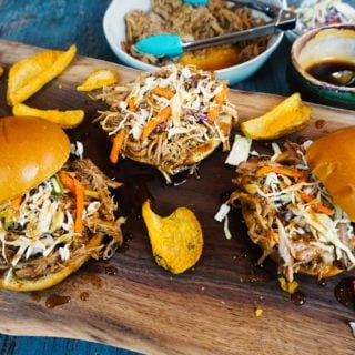 Three pulled pork sandwiches on a cutting board